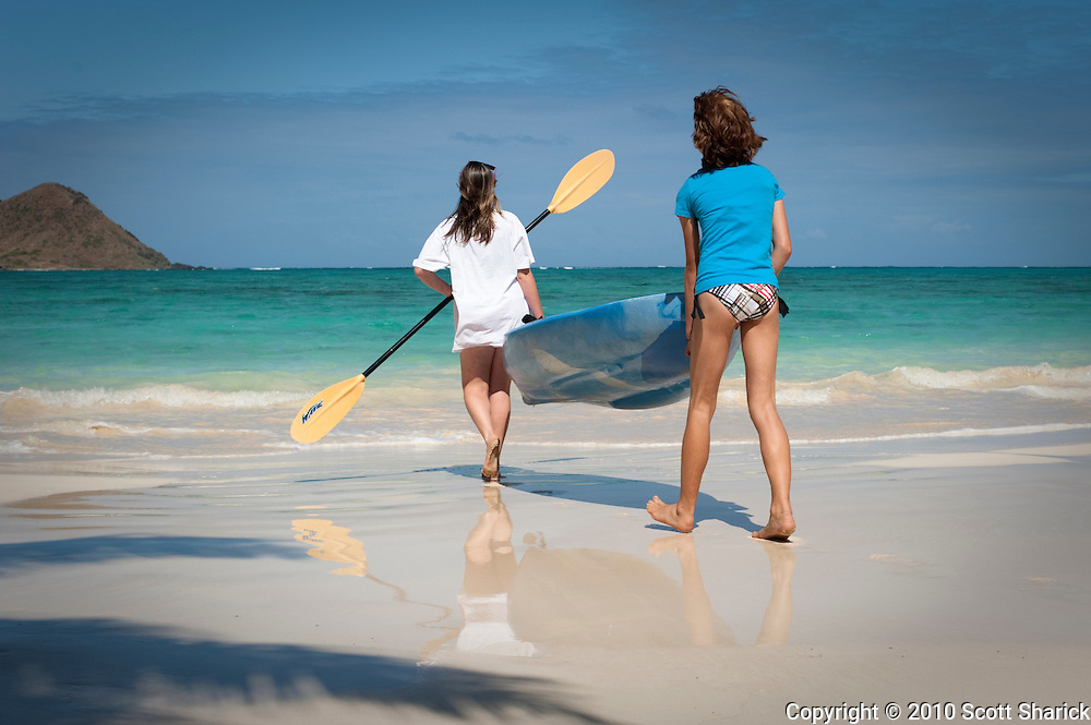 Two girls carrying a kayak at Lanikai Beach on Oahu, Hawaii.
