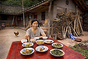 Lan Guihua, a widowed farmer, in front of her home with her typical day's worth of food in Ganjiagou Village, Sichuan Province, China. (From the book What I Eat: Around the World in 80 Diets.) The caloric value of her day's worth of food on a typical day in June was 1900 kcals. She is 68 years of age; 5 feet, 3 inches tall; and 121 pounds. Her farmhouse is tucked into a bamboo-forested hillside beneath her husband's grave, and the courtyard opens onto a view of citrus groves and vegetable fields. Chickens and dogs roam freely in the packed-earth courtyard, and firewood and brush for her kitchen wok are stacked under the eaves. Although homegrown vegetables and rice are her staples, chicken feathers and a bowl that held scalding water for easier feather plucking are clues to the meat course of a special meal for visitors. In this region, each rural family is its own little food factory and benefits from thousands of years of agricultural knowledge passed down from generation to generation. MODEL RELEASED.