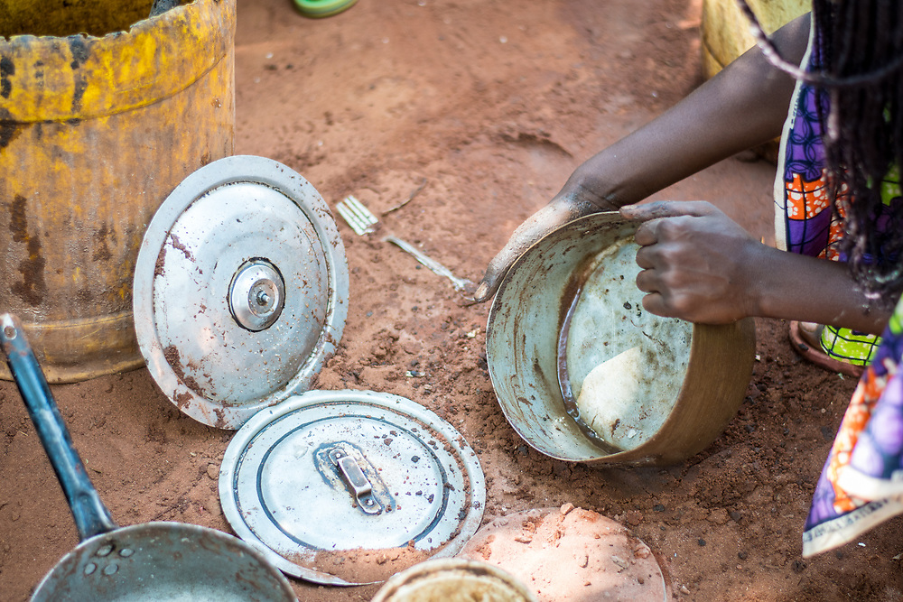 Hands of Zambian woman as she cleans up metal pots used for cooking, Mukuni Village, Zambia