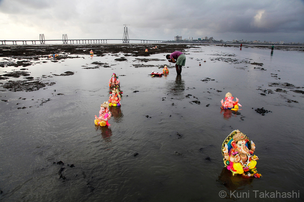 A hindu devotee pray as he leaves a ganesha idle in the sea in Mumbai, India on Sep 12, 2010 on the 2nd day of Ganpati festival. The 10-day hindu festival, celebrating the birthday of Lord Ganesha who is widely worshiped as the god of wisdom, prosperity and good fortune, attracts tens of thousands people..Photo by Kuni Takahashi