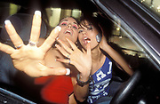Two girls inside a car, one with a mobile phone, pushing their hands to the camera, UK 2004