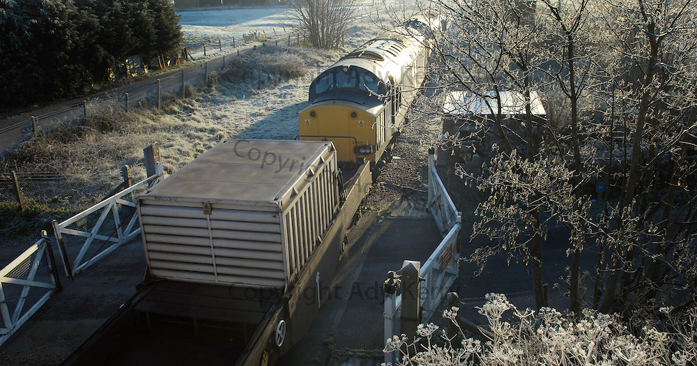 "A train on its way to the Nuclear Power Station at Dungeness to collect rods for reprocessing travels through the village of Lydd, nr Dungeness, Kent, 20th December 2006. Dungeness ""A"" is to be shut down for the last time on December 31st 2006, with de-commissioning starting in 2007."