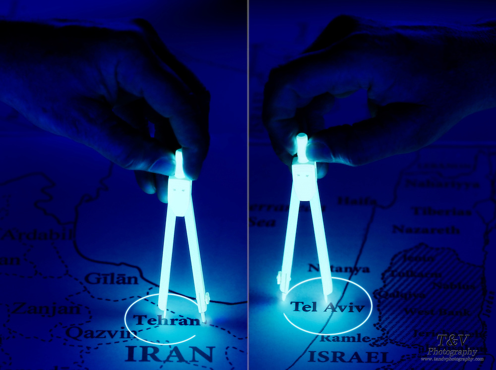 Opposiing images of hands using glowing compasses to draw circles around the cities of Tehran and Tel Aviv.Black light