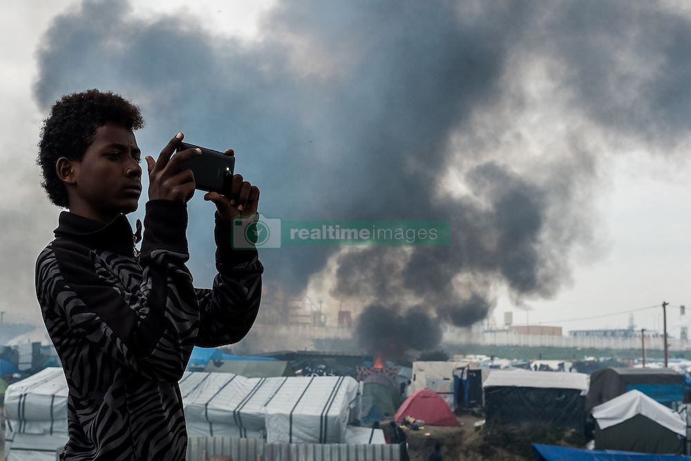 October 26, 2016 - Calais, France - A Migrant films in the Calais Jungle the fires, on October 26, 2016. Huge fires destroyed a mayor part of the refugee camp today. (Credit Image: © Markus Heine/NurPhoto via ZUMA Press)