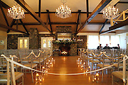 Indoor wedding ceremony site with chandeliers, fireplace adorned with flowers, wood floor aisle lined with glass tumblers and floating candles and silver chiavari chairs at Crooked Lake House, Averill Park, NY
