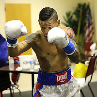 Professional boxer Orlando Cruz, the sports first openly gay fighter, prepares in his locker room prior to his match against Gamalier Rodriguez for the NABO Featherweight Title at the Bahia Shriners Center on Saturday, April 19, 2014 in Orlando, Florida.  (AP Photo/Alex Menendez)