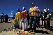 An Apache girl dances with her godmother and godfather at her Sunrise Dance, a first menstruation rite, on the San Carlos Apache Reservation, Arizona, USA. The three are covered with sacred yellow pollen from the cattail plant, which has been applied as a blessing by the medicine man and the relatives. The Sunrise Dance is an enactment of the Apache creation myth and during the rites the girl 'becomes' Changing Woman, a mythical female figure, and comes into possession of her healing powers. The rites are also supposed to prepare the girl for adulthood and to give her a long and healthy life without material wants.