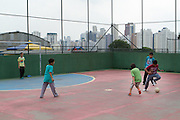 Children playing football at Instituto Cristóvan School in São Paulo, Brazil. Missão Paz, an organisation that works in partnershp with C&A Foundation, pays for children to attend the school so that parents who are working in the textile industry can get on and work without worrying about looking after their childen at the same time.