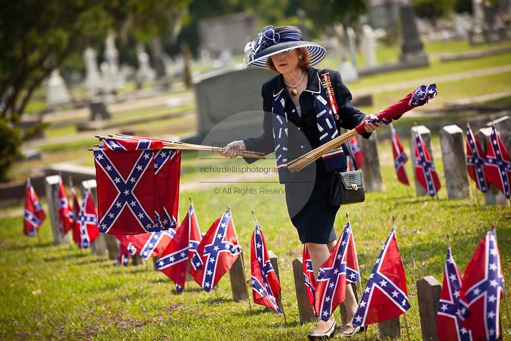A member of the Daughters of the Confederacy removes Confederate flags on tombs of soldiers killed during the US Civil War at Magnolia Cemetery to mark Confederate Memorial Day on May 10, 2011 in Charleston, South Carolina.  South Carolina is one of three states that marks the day as a public holiday.