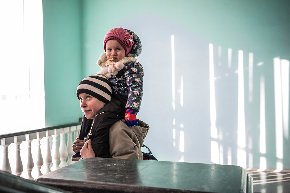 A boy displaced by fighting around the town of Debaltseve carries a young girl on his shoulders on Thursday, February 12, 2015 in Kharkiv, Ukraine. The group spent several hours in Kharkiv before boarding a train that will take them to Lviv, on the Western side of the country.