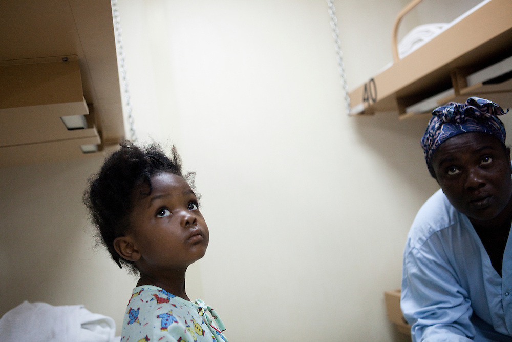 A four-year-old Haitian girl recouperates from a bout of diarrhea with her mother in the pediatric ward on board the USNS Comfort, a U.S. Naval hospital ship, on January 21, 2010 in Port-au-Prince, Haiti. The Comfort deployed from Baltimore with 550 medical personnel on board to treat victims of Haiti's recent earthquake, and arrived on January 20.
