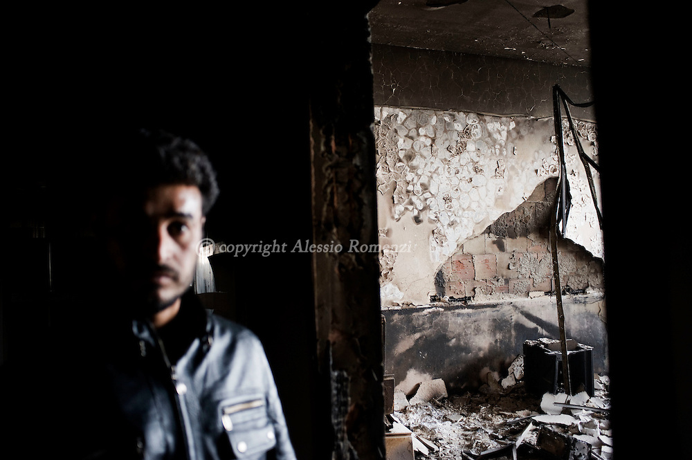 A Libyan man looks on as he walks through a burnt down police station in Benghazi, Libya on February 25, 2011..ALESSIO ROMENZI