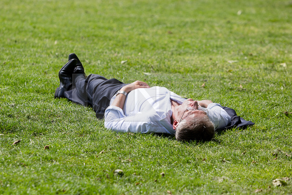 © Licensed to London News Pictures. 12/05/2016. LONDON, UK.  A man relaxes on the grass during warm sunny weather in Green Park at lunchtime.  Photo credit: Vickie Flores/LNP