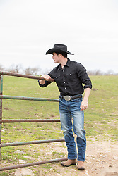 cowboy by a rustic fence on a ranch