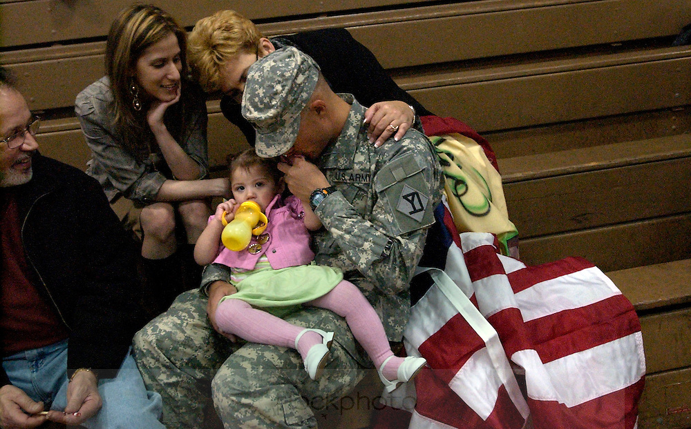 A U.S. Army soldier returns home to his family at the Cambridge National Guard Armory, March 20, 2008.