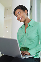 Business woman using laptop sitting on window ledge, low angle view
