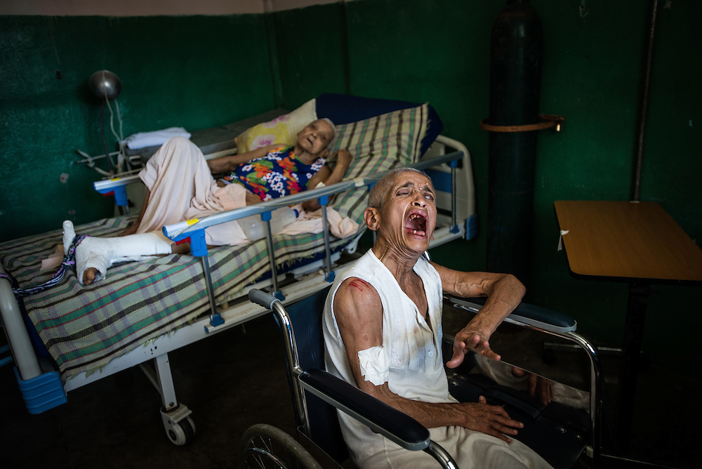 "BARQUISIMETO, VENEZUELA - AUGUST 24, 2016: Emiliana Rodríguez screams at the top of her lungs over and over again, ""I'm NOT crazy, I'm just HUNGRY!""  Mrs. Rodríguez is a hospitalized schizophrenic who doctors say functioned well when she had medication, but that she has sunk into a delusional state and can no longer even walk, confined to a broken wheel. She had fallen out of her chair shortly before this photo was taken, and her shoulder and mouth were both bleeding.  Mrs. Rodriguez currently only receives two of the six medications she was prescribed. The other 4 cannot be found because of shortages. ""The disease has taken her over,"" said Évila García, the chief nurse. There is also no medication for her glaucoma which staff said had left her hardly able to see. PHOTO: Meridith Kohut"