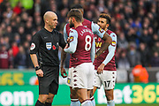 Henri Lansbury of Aston Villa speaks to referee Peter Bankes during the Premier League match between Wolverhampton Wanderers and Aston Villa at Molineux, Wolverhampton, England on 10 November 2019.