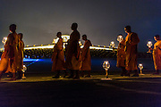 "14 FEBRUARY 2014 - KHLONG LUANG, PATHUM THANI, THAILAND: Buddhist monks participate in the evening candle light procession for Makha Bucha Day at Wat Phra Dhammakaya. The aims of Makha Bucha Day are: not to commit any kind of sins, do only good and purify one's mind. It is a public holiday in Cambodia, Laos, Myanmar and Thailand. Many people go to the temple to perform merit-making activities on Makha Bucha Day. The day marks four important events in Buddhism, which happened nine months after the Enlightenment of the Buddha in northern India; 1,250 disciples came to see the Buddha that evening without being summoned, all of them were Arhantas, Enlightened Ones, and all were ordained by the Buddha himself. The Buddha gave those Arhantas the principles of Buddhism, called ""The ovadhapatimokha"". Those principles are:  1) To cease from all evil, 2) To do what is good, 3) To cleanse one's mind. The Buddha delivered an important sermon on that day which laid down the principles of the Buddhist teachings. In Thailand, this teaching has been dubbed the ""Heart of Buddhism."" Wat Phra Dhammakaya is the center of the Dhammakaya Movement, a Buddhist sect founded in the 1970s and led by Phra Dhammachayo.    PHOTO BY JACK KURTZ"