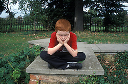 8 year old boy sitting cross legged on wall with head in hands; looking fed up UK. MR