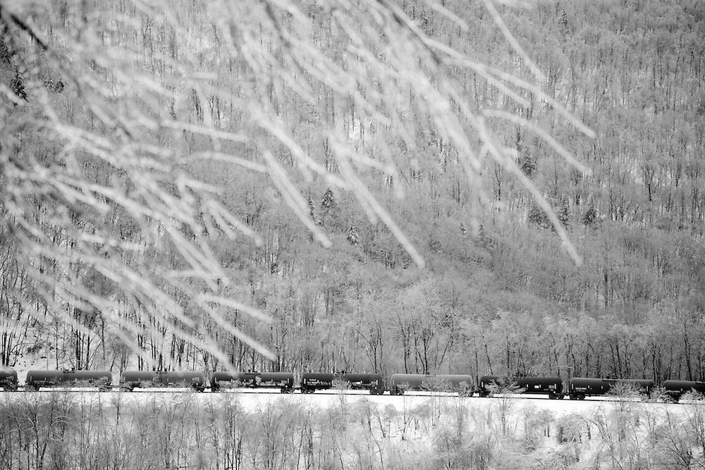 An oil train heads east through Horseshoe Curve amid an ice covered landscape of silver trees.
