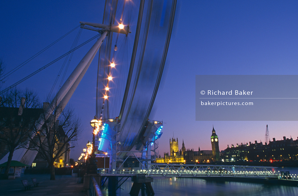 The ever-turning London Eye is seen over the River Thames with the Palace of Westminster and Parliament beyond. The wheel is blurred after a minute's exposure and the blue sky behind renders evening as a romantic cityscape backdrop. We see Big Ben in the Tower of Westminster and Parliament just as they have become floodlit and the stand out set against the other buildings, very easily recognised as the iconic London landmarks known around the world. The Eye, or as it was known in 2000, the Millennium Wheel, was designed by architects David Blian, Julia Barfield, Malcolm Cook, Mark Sparrowhawk, Steven Chilton and Nic Bailey, and carries 32 sealed, air-conditioned passenger capsules which rotate at 0.26 metres (0.85 feet) per second (about 0.9 km/h or 0.5 mph) so that one revolution takes about 30 minutes.
