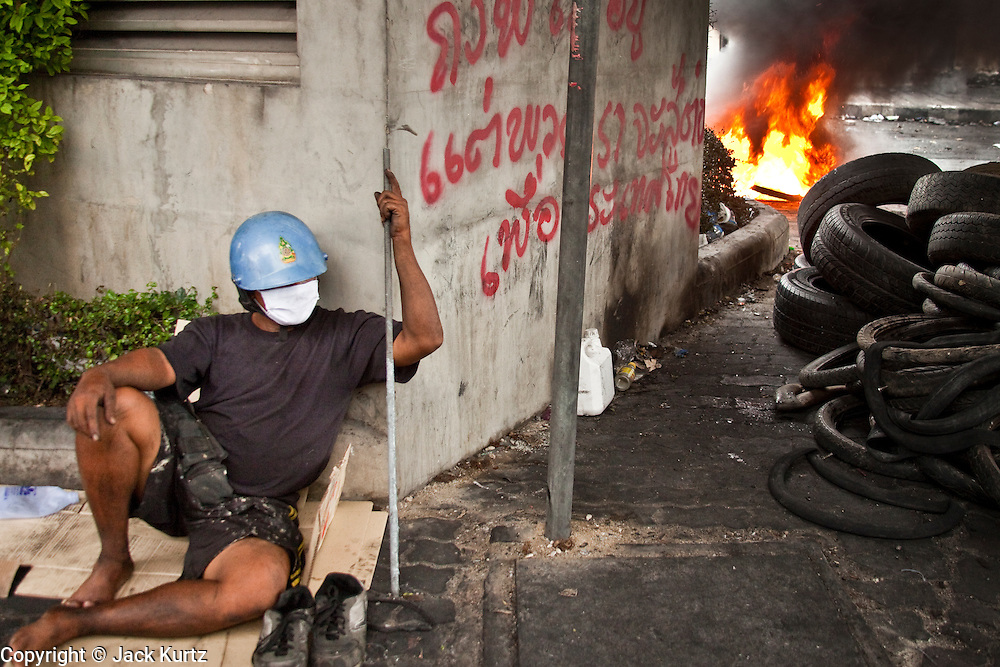18 MAY 2010 - BANGKOK, THAILAND: A protester sleeps near a burning tire barricade at Din Daeng Intersection in Bangkok Tuesday. The intersection has been under periodic sniper fire from unidentified snipers near Thai military lines. Violent unrest continued in Bangkok again Tuesday nearly a week after Thai troops started firing on protesters and Bangkok residents took to the streets in violent protest against the government. Tuesday was not as violent as previous days however. Although protesters continued to set up roadblocks and flaming tire barricades across parts of the city, there was not as much gunfire from the government lines. The most active protesters were at the Din Daeng Intersection about a mile from the Red Shirts' Ratchaprasong camp.  PHOTO BY JACK KURTZ