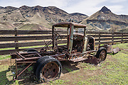 A broken, antique rusting car with flat tires rusts at James Cant Ranch Historic District, Sheep Rock Unit, John Day Fossil Beds National Monument, Oregon, USA. The Cant Ranch interpretive site shows visitors an early 1900s livestock ranch. James Cant owned the ranch from 1910 to 1975, after which he sold to the National Park Service.
