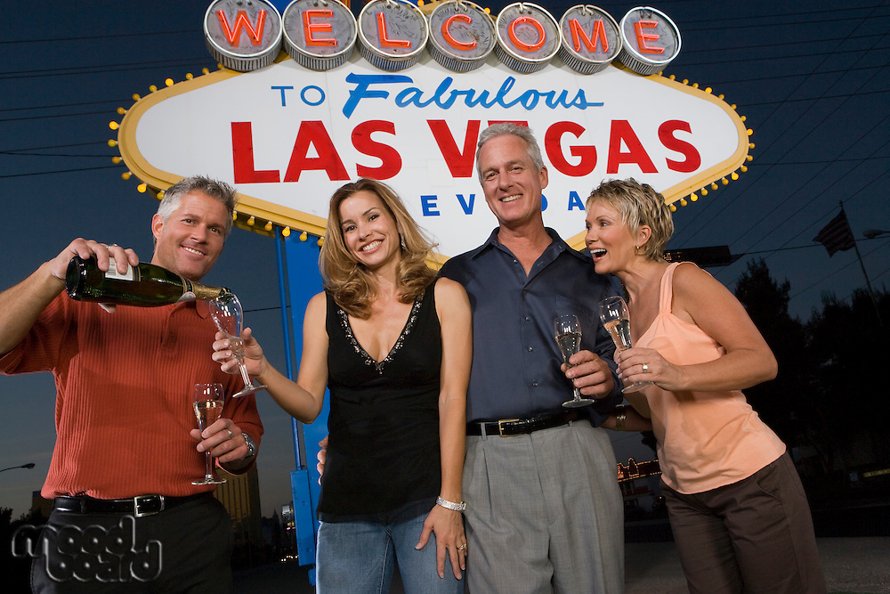 Two women and two men posing in front of Welcome to Las Vegas sign