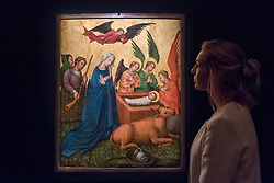 "© Licensed to London News Pictures. 01/12/2017. London, UK.  A staff member views ""The Master of the Saint Lambrecht Votive Altarpiece, Recto: The Nativity"", circa 1435-40, (Est. GBP300-400k).  Preview of ""Masters of Light"", Sotheby's Old Masters Evening Sale which will take place on 6 December at Sotheby's, New Bond Street. Photo credit: Stephen Chung/LNP"