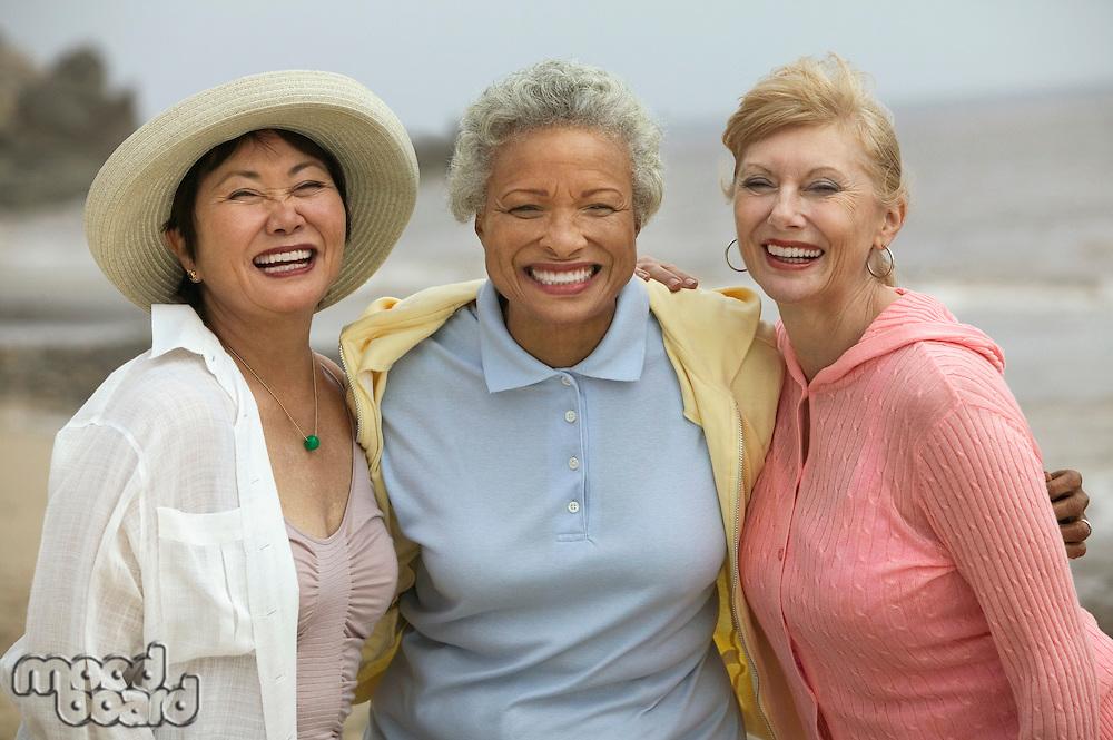 Three female friends embracing at beach (portrait)