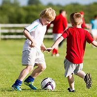 Two young supporters enjoying a kick around at half time during the Ennis Town V Newmarket on Fergus Clare Cup Final 2014 at the county grounds, Ennis