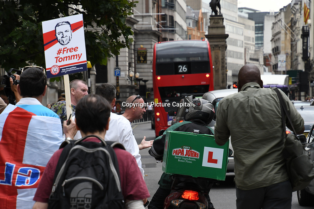 Alt-right push a pizza delivery man of the bike during the Lord Justice Leveson hearing Tommy's appeal outside the Royal court of Justice on 18th July 2018 in London, UK.