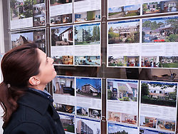 Woman looking at houses for sale in estate agents window in Utrecht The Netherlands
