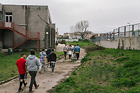 """NAPLES, ITALY - 16 MARCH 2018: Teenagers followed by their instructors walk out of the gym after practicing parkour at """"Il Tappeto di Iqbal"""" (Iqbal's carpet), a non-profit cooperative in Barra, the estern district of Naples, Italy, on March 16th 2018.<br /> <br /> Il Tappeto di Iqbal (Iqbal's Carpet) is a non-profit cooperative founded in 2015 and Save The Children partner since 2015 that operates in the Naple's eastern neighborhood of Barra children in the arts of circus, theater and parkour. It was named after Iqbal Masih, a Pakistani boy who escaped from life as a child slave and became an activist against bonded labor in the 1990s.<br /> Barra, which is home to some 45,000 people, has the highest rate of school dropouts in the Italian region of Campania. Once a thriving industrial community, many of the factories were destroyed in a 1980 earthquake and never rebuilt. The resulting de-industrialization turned Barra into a poor, decaying neighborhood. There are no cinemas, theaters, parks or public spaces in Barra.<br /> The vast majority of children from poor families are faced with the choice of working in the black economy or joining the ranks of the organised crime.<br /> Recently, Save the Children Italy opened a number of educational and social spaces in Barra. The centers, known as Punti Luce, or points of light, aim to help local kids stay out of the ranks of the organised crime and have also become hubs for Iqbal's Carpet to work."""