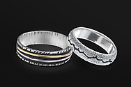 A set of silver rings on black background. Table top.