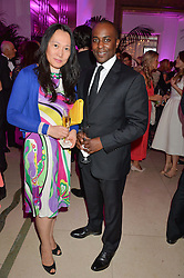 YIMEI McCABE Chairman of HK WHM Hampers Ltd and tailor CHRISTOPHER CHILDS at the QBF Spring Gala in aid of the Red Cross War Memorial Children's Hospital hosted by Heather Kerzner and Jeanette Calliva at Claridge's, Brook Street, London on 12th May 2015.