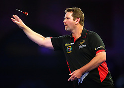 Craig Ross throws during his match with Toni Alcinas during day three of the William Hill World Darts Championships at Alexandra Palace, London.