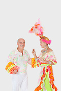 Happy senior dancing couple in Brazilian outfits dancing over gray background