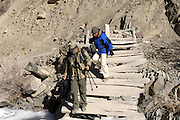 Leh - Wednesday, Nov. 29, 2006: Lorna Brooks and Dr Raghunandan Singh Chundawat climb down a broken bridge in the Rumbak Valley, Ladakh. (Photo by Peter Horrell / www.peterhorrell.com)