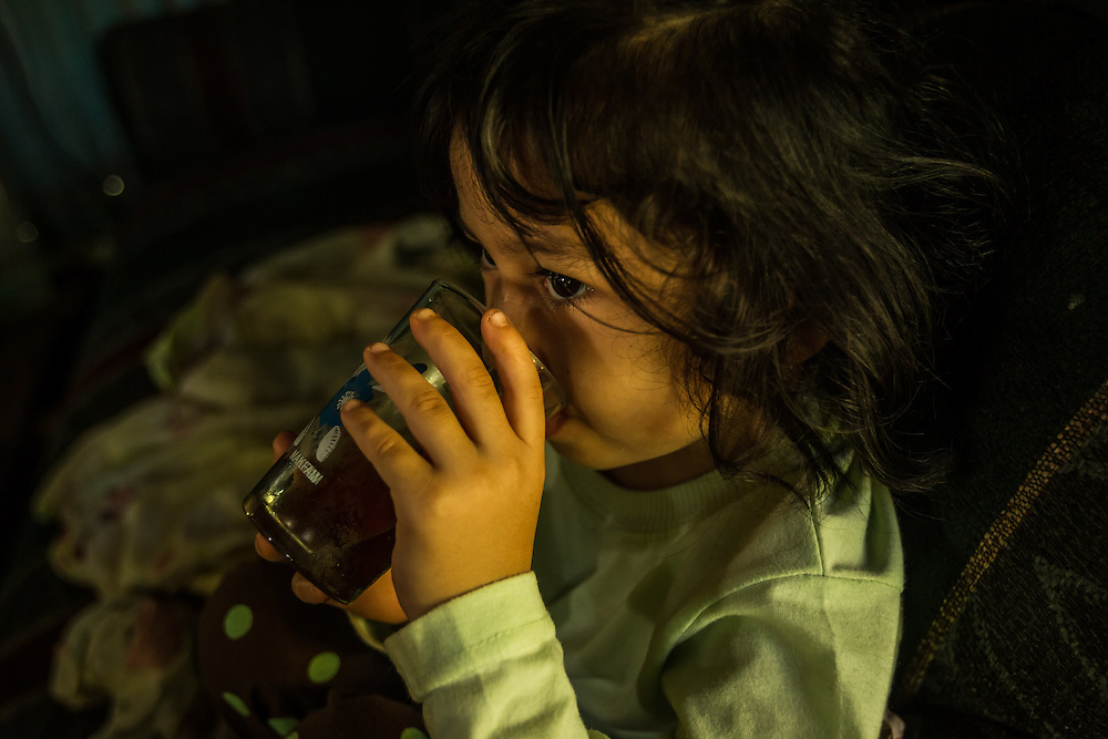 A young girl drinks water mixed with brown sugar for breakfast, in a  small town where a nearby pineapple industrial farm operates.  Residents believe their water to be contaminated because of environmental failures at the pineapple plantation.