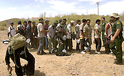 U. S. Border patrol agents process illegal immigrants, who crossed from Mexico on to the Tohono O'odham Nation in Arizona, for deportation from Sells.