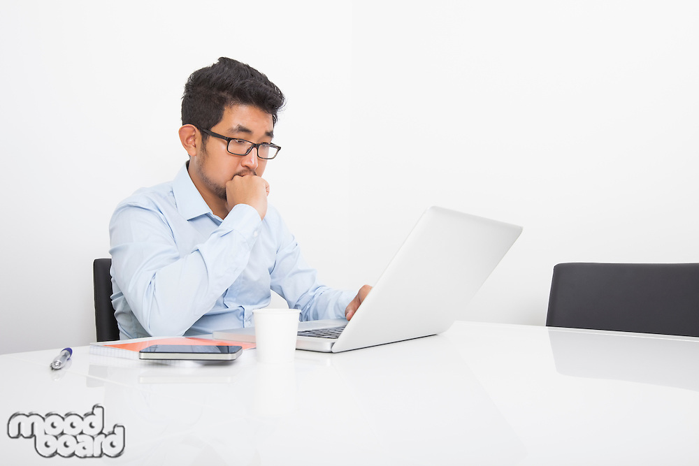 Young businessman working on laptop at desk in office