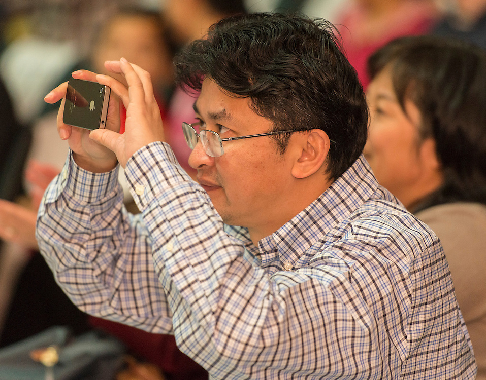 An audience member captures the performance during a district wide celebration of the Chinese New Year at Sharpstown International School, February 22, 2014.