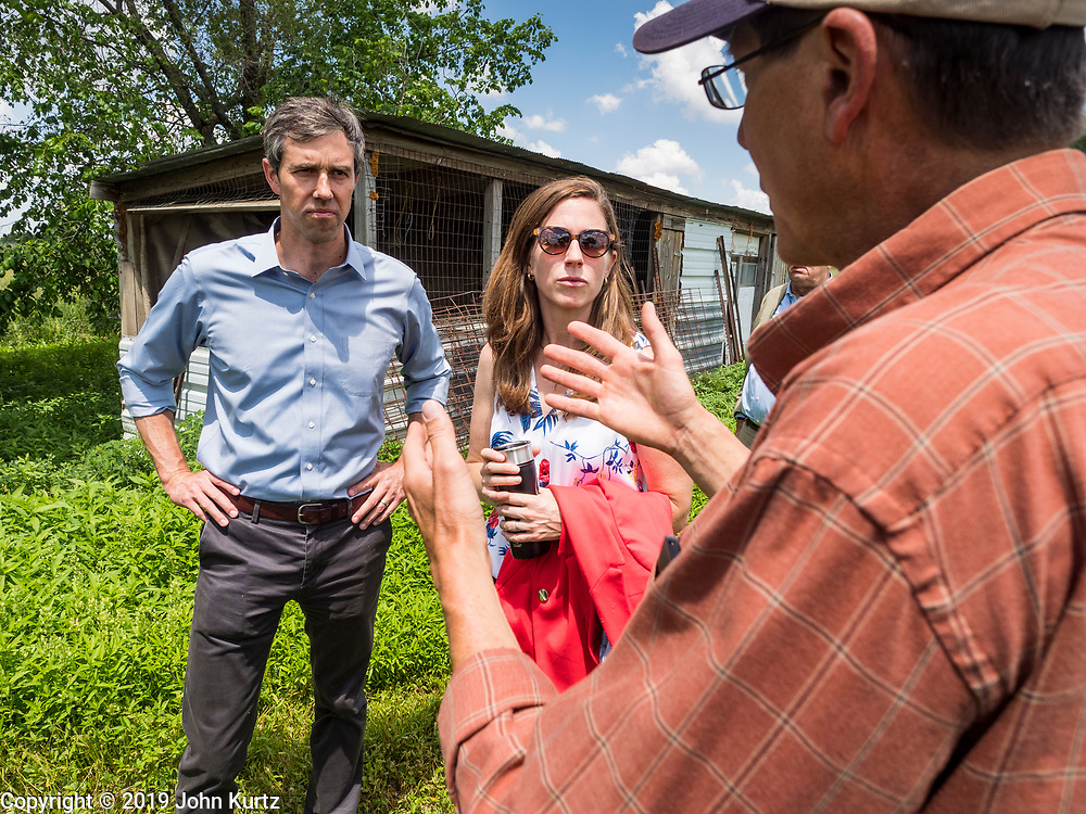 07 JUNE  2019 - LACONA, IOWA: BETO O'ROURKE, left, his wife, AMY O'ROURKE, and MATT RUSSELL talk while they tour Russell's farm, Coyote Run Farm. O'Rouke toured Coyote Run Farm in Lacona Friday. He talked to Russell, the farm's co-owner, about the impact of President Trump's tariffs on Iowa farmers and how climate change was changing American agriculture. O'Rourke, running to be the 2020 Democratic nominee for the US Presidency, has made climate change a central part of his campaign. Iowa traditionally hosts the the first selection event of the presidential election cycle. The Iowa Caucuses will be on Feb. 3, 2020.                               PHOTO BY JACK KURTZ