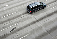 View of cracked and worn concrete highway with moving mini van.
