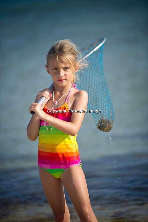 A young girl holds a net after catching a blue crab.
