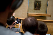 Tourist listens and learns with a guided tour commentary about the Mona Lisa using free Nintendos in the Louvre, Paris.
