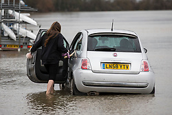 © Licensed to London News Pictures. 02/01/2018. London, UK. A woman wades through flood water to rescue her car on the embankment at Putney in West London where the River Thames has broken its banks. Photo credit: Rob Pinney/LNP