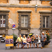 Five women sitting on a bench in the piazza listening to a man tell a story in Orvieto, Itay as a young woman looks on from behind - no release available